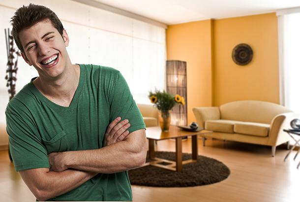 Jongere met een verstandelijke beperking lachend in zijn zelfstandige woonruimte