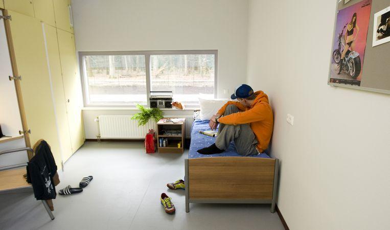 Jongere met verstandelijke beperking zittend op bed in zijn kamer