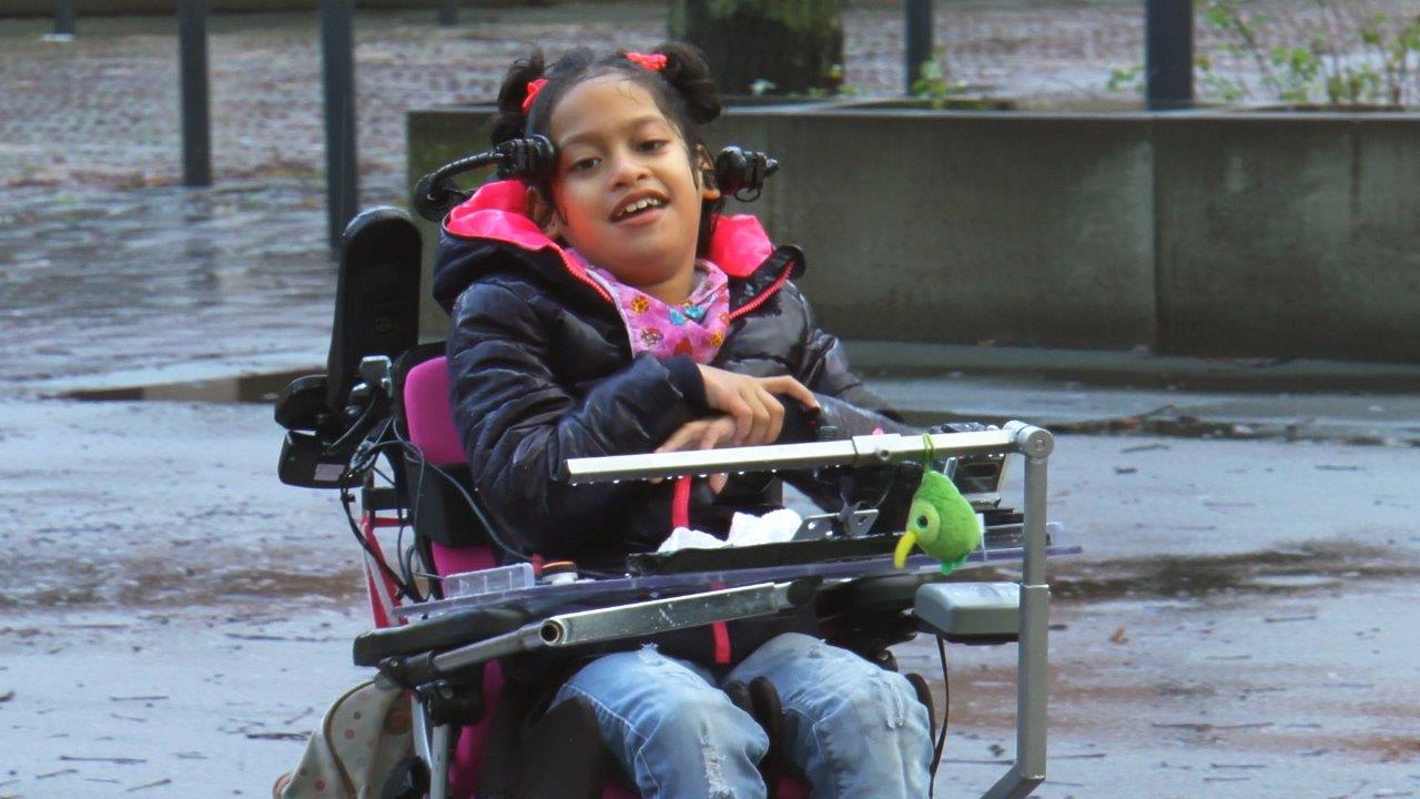 Noa, een meisje met een meervoudige beperking in haar rolstoel