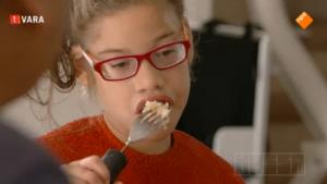 Meervoudig gehandicapt meisje eet onder begeleiding
