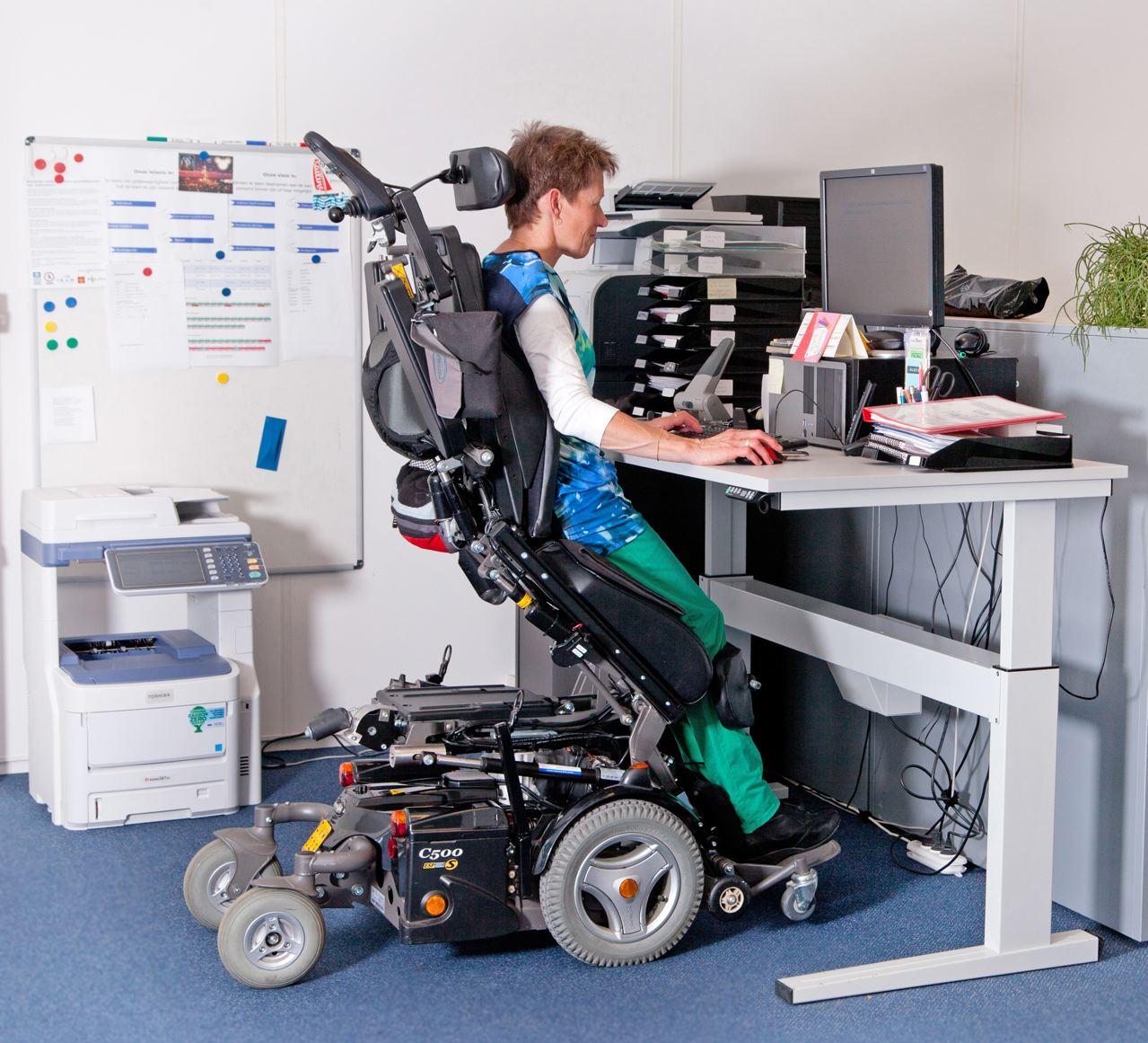 Mevrouw met een beperking aan het werk met speciaal aangepast bureau
