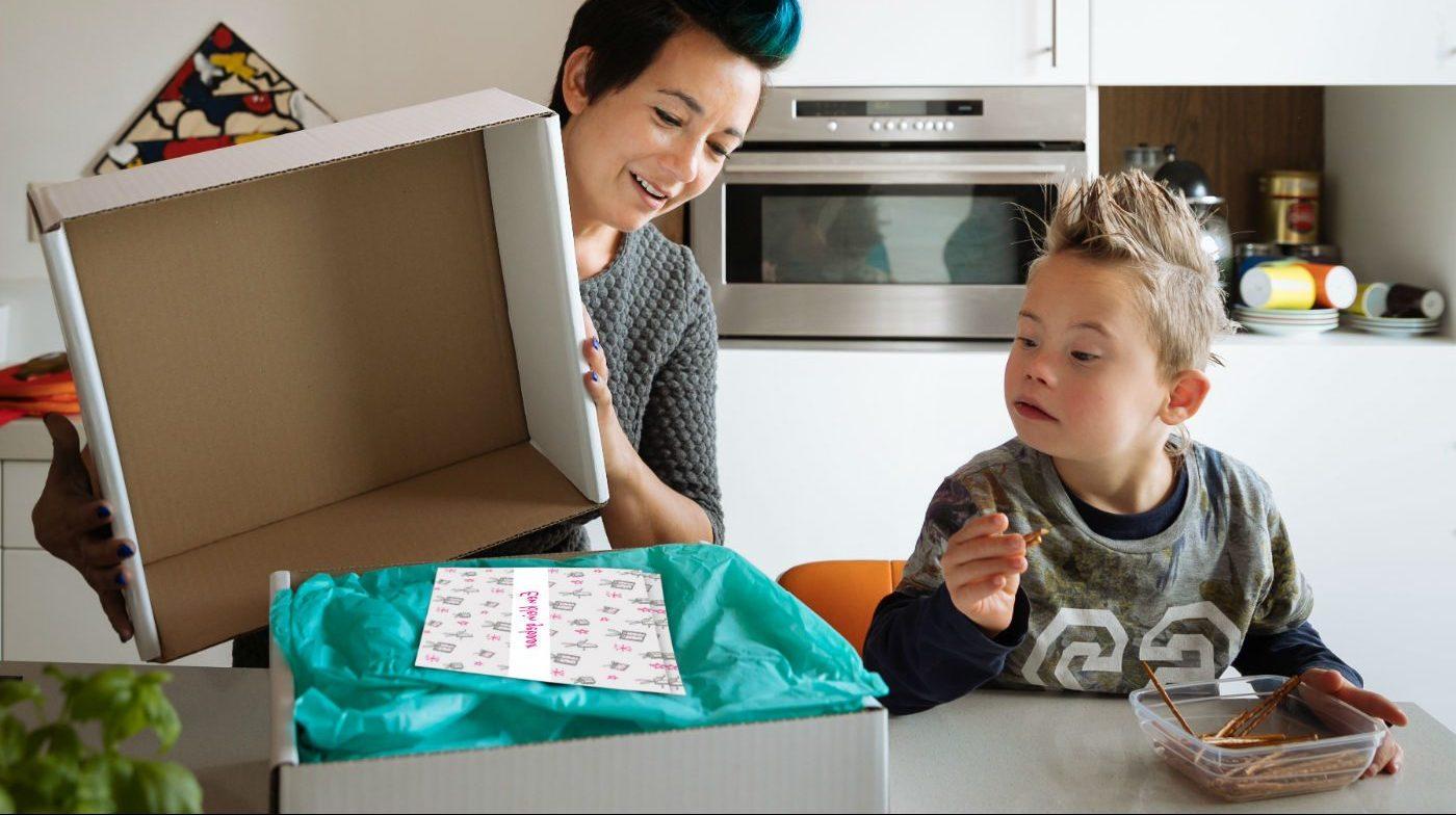 Mantelzorger pakt samen met zoontje verwenbox van HandicapNL uit.