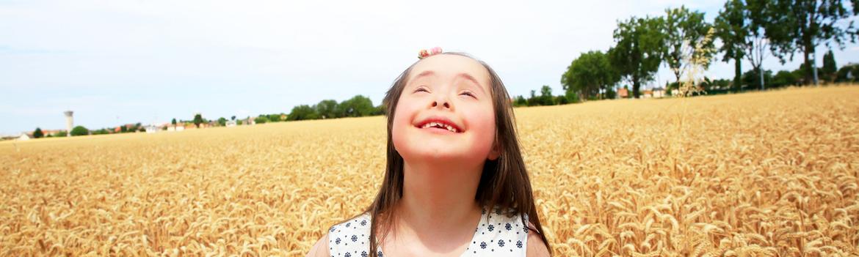 Meisje met syndroom van Down in korenveld