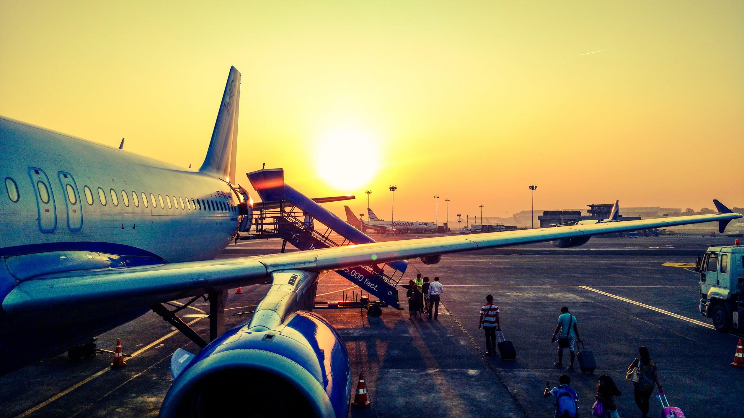 Foto van vliegtuig op vliegveld met op achtergrond zonsondergang.