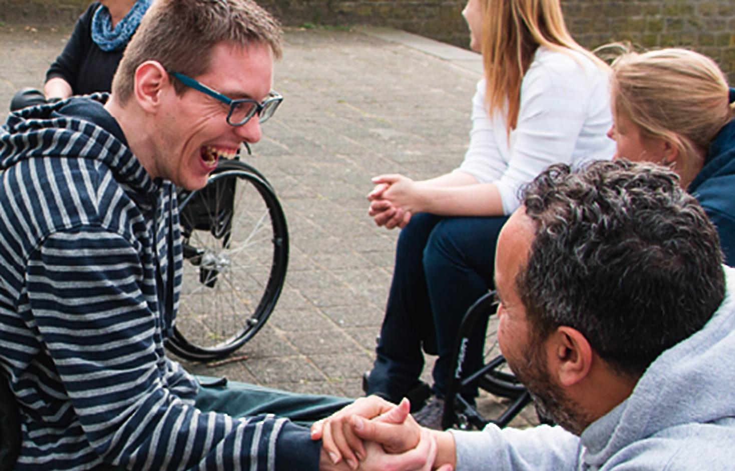 Lachende jongeren tijdens de rolstoeltraining.