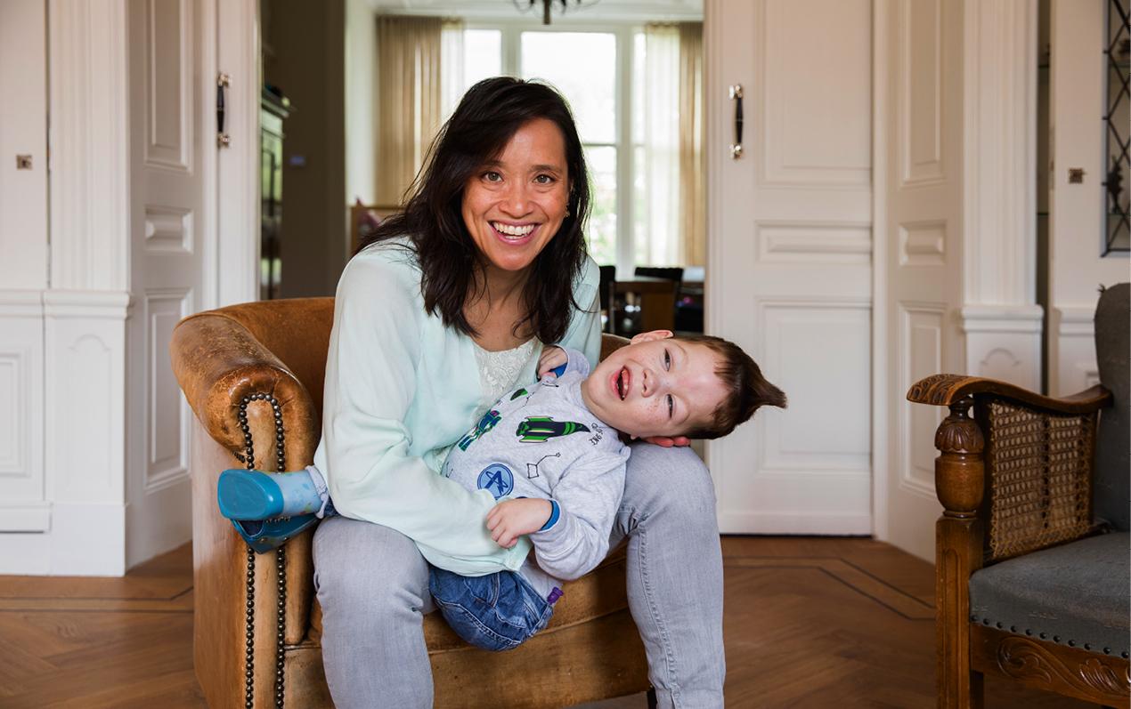 Vanessa de Vries lachend met haar zoon met EMB op schoot.