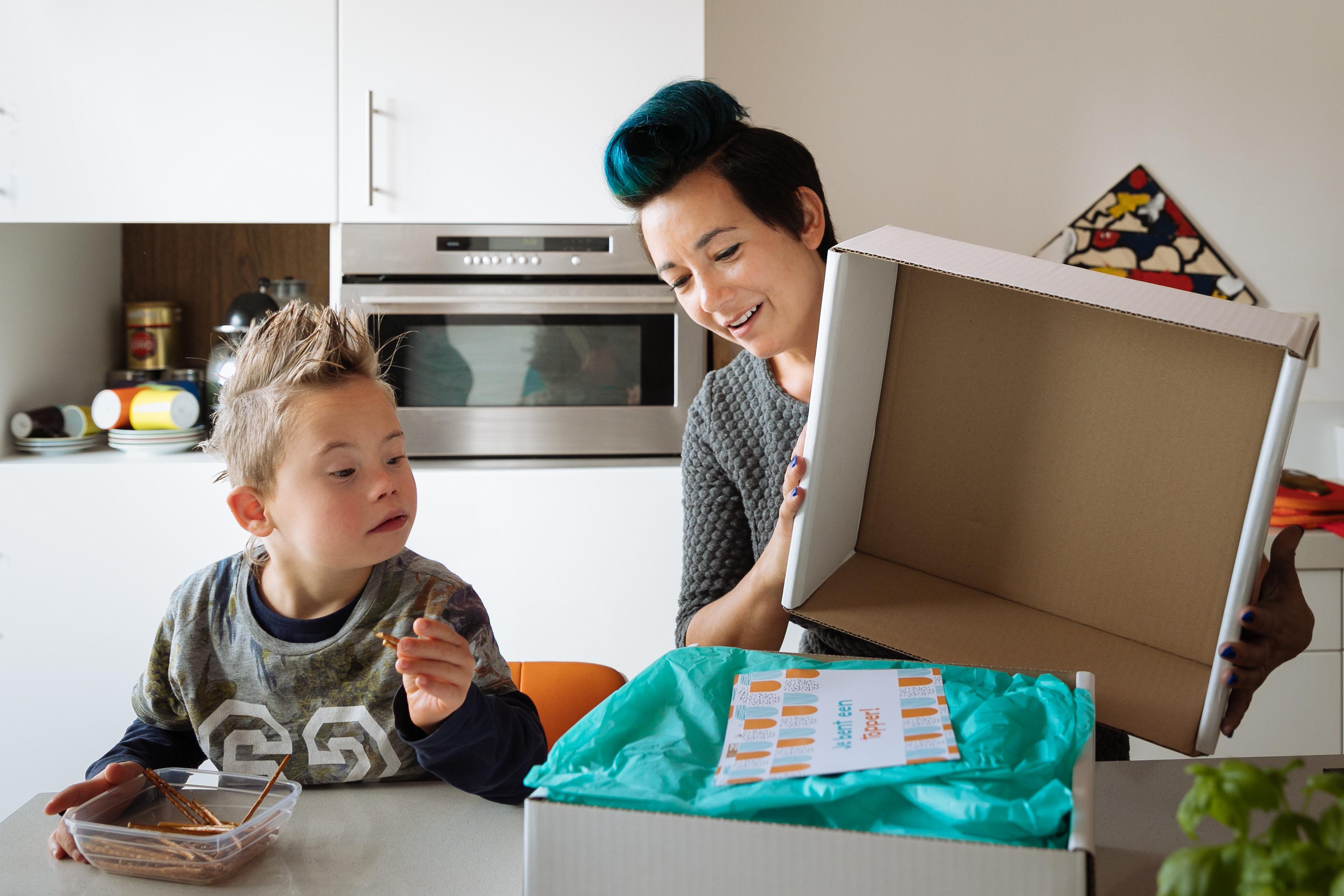 Mevrouw maakt samen met zoon doos Gebaar van Waardering open.