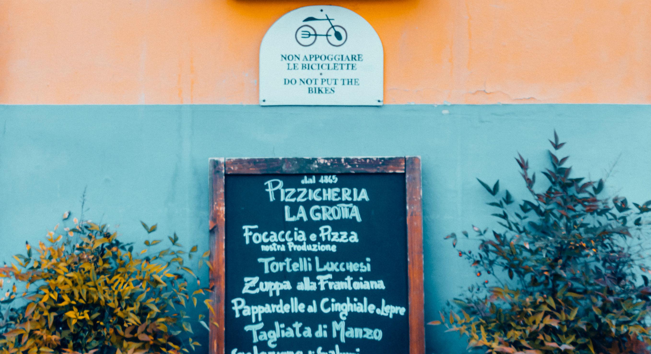 Italiaans straatje met menu van een pizzaria.