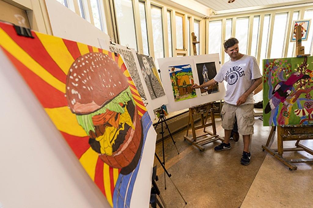 Schilderijen van het Buiten Gewoon Kunst met een kunstenaar.