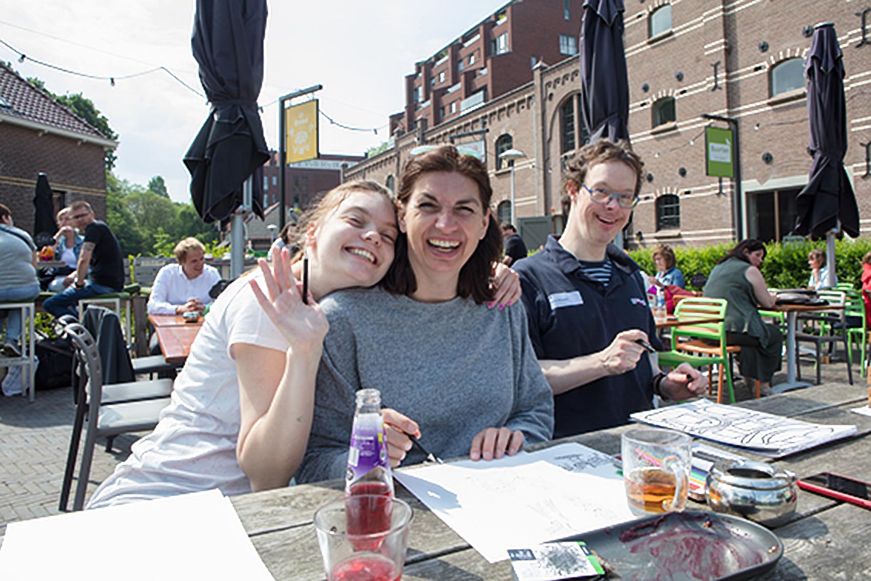 Derk samen met twee lachende dames tekenen buiten aan een picknicktafel.