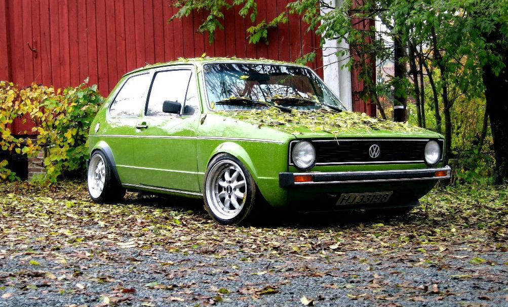 Foto van een groene Volkswagen Golf bedekt met bladeren in herfstlandschap.