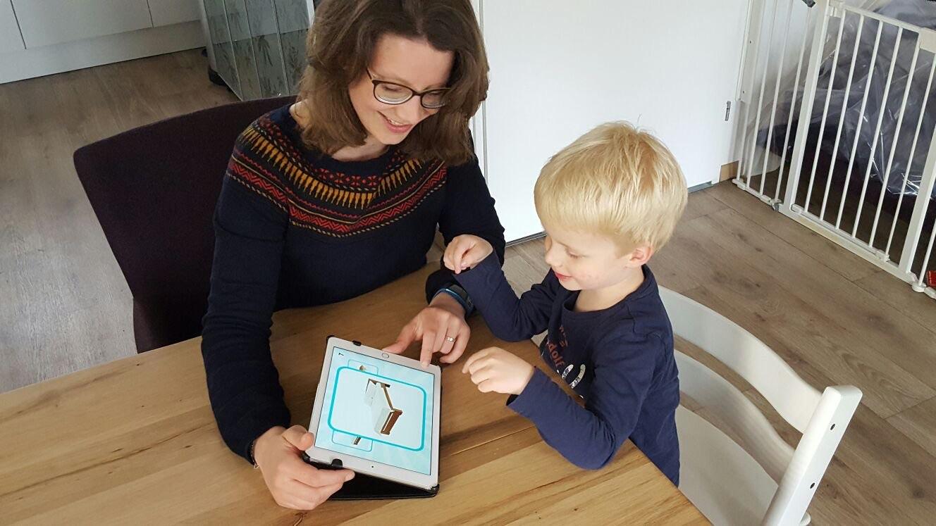 Moeder en Zoon gebruiken Speakaboo op de iPad aan tafel.