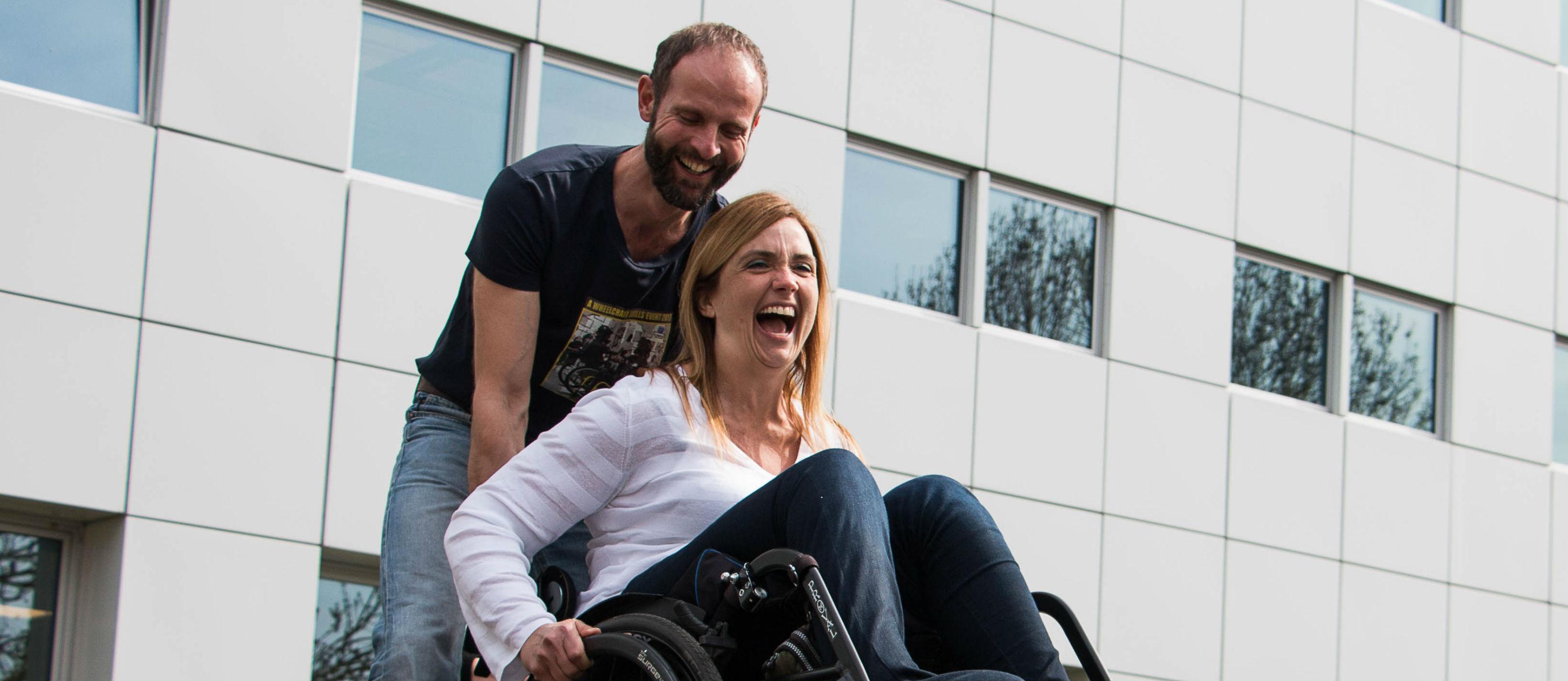 Fysiotherapeut Gert Rots geeft rolstoeltraining en duwt een lachende vrouw in rolstoel voorzichtig naar beneden.