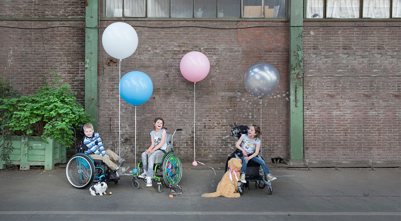 Drie kinderen met een ernstig meervoudige beperking in een rolstoel