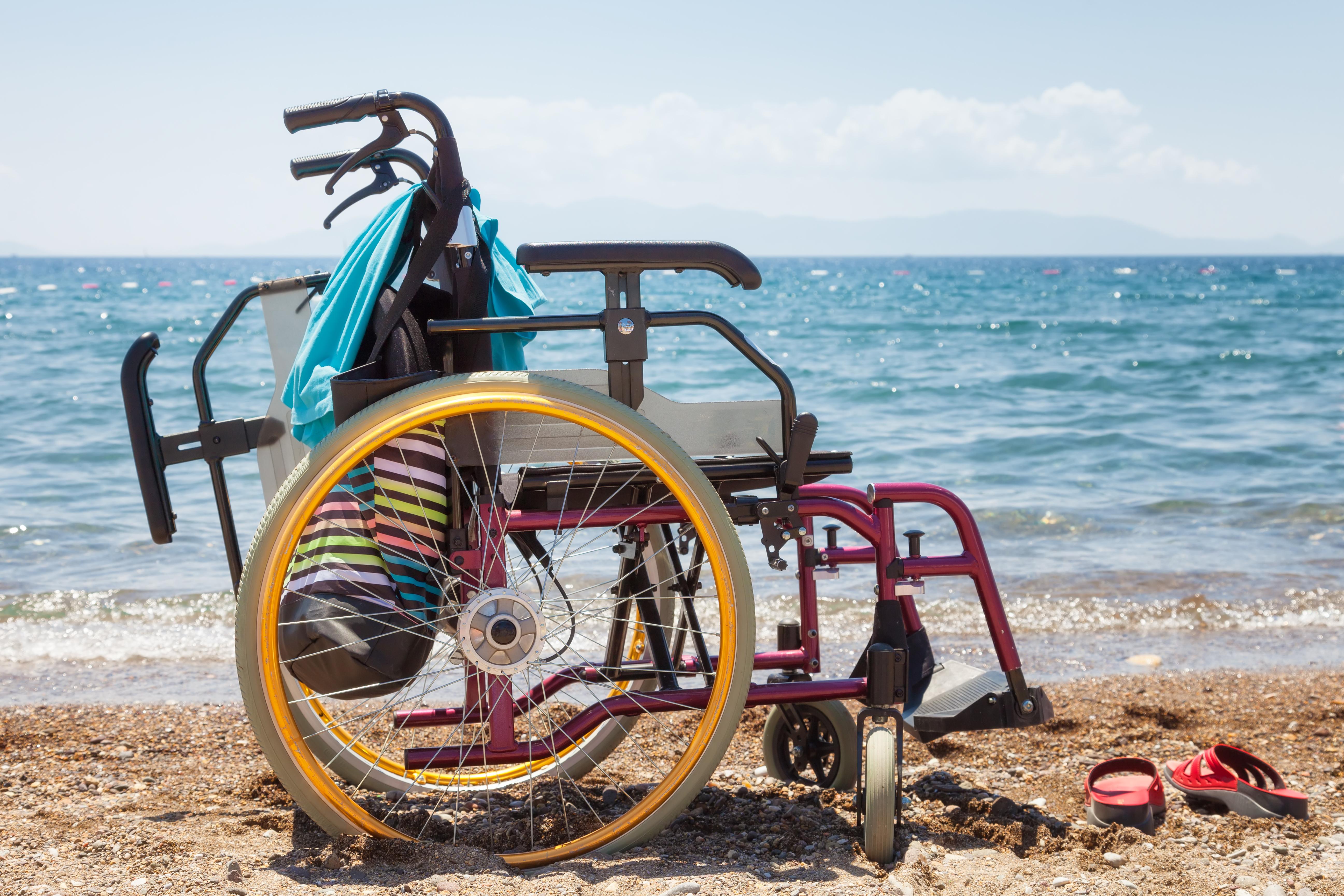 Een lege rolstoel op het strand omgeven met strandspullen, zoals een handdoek en slippers.