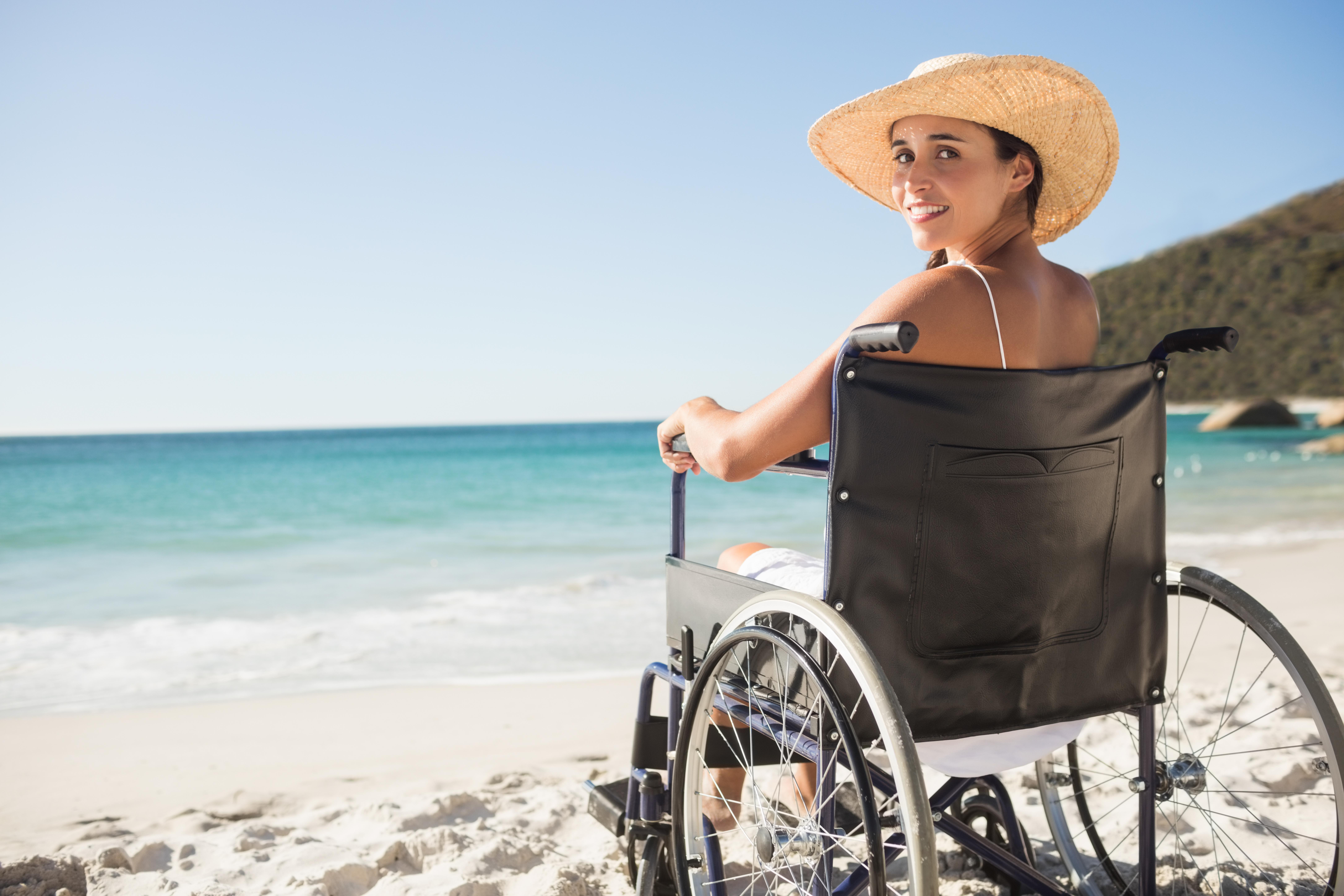 Jonge vrouw in een rolstoel op het strand.