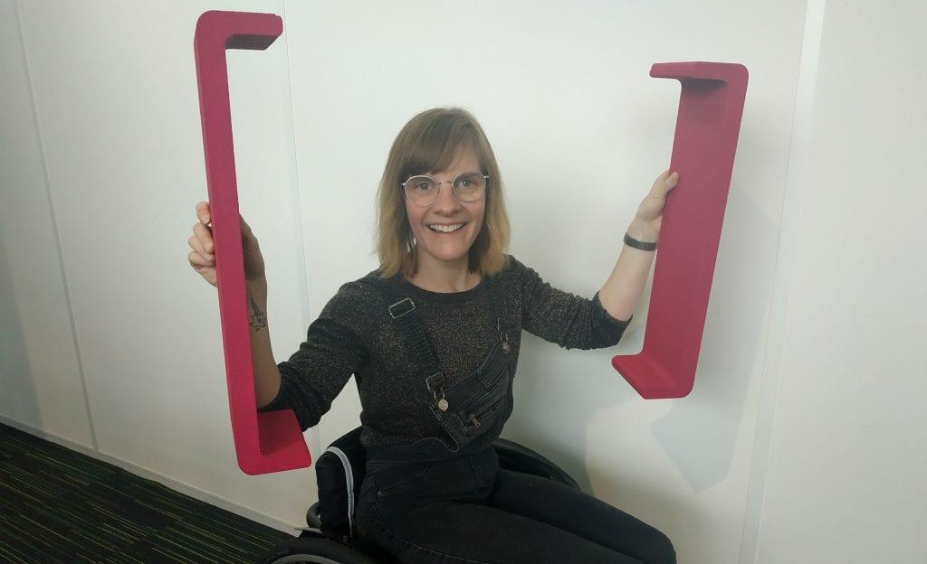 Een lachende Léonie (in rolstoel) op de foto met de twee haken uit het logo van HandicapNL.