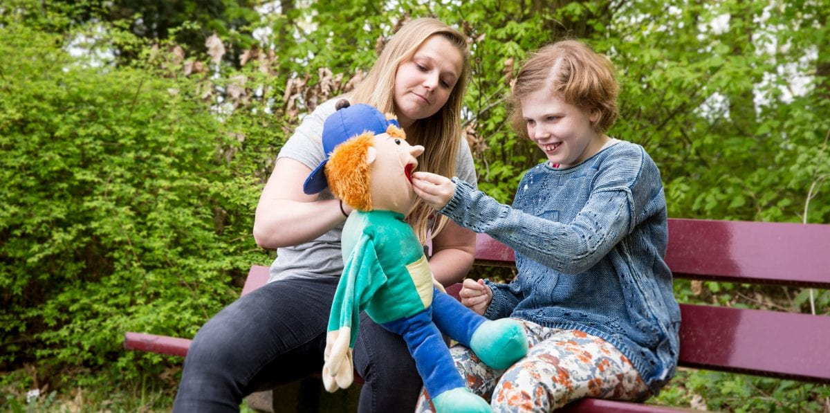 Meisje met pop en begeleider op Wielewaalvakantie