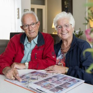Gerrie en Sjef bekijken foto's aan de koffietafel.