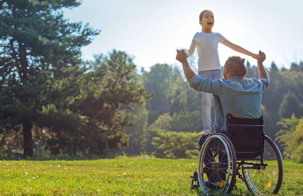 Man in rolstoel met kind staand op zijn schoot