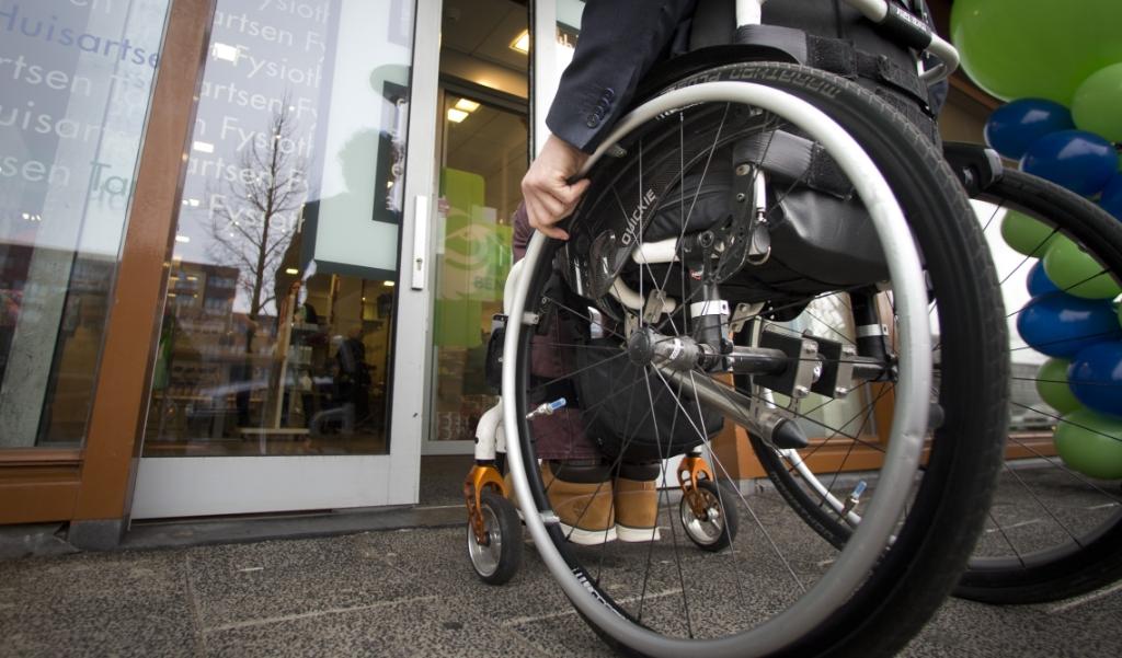 Iemand in rolstoel voor automatische schuifdeur