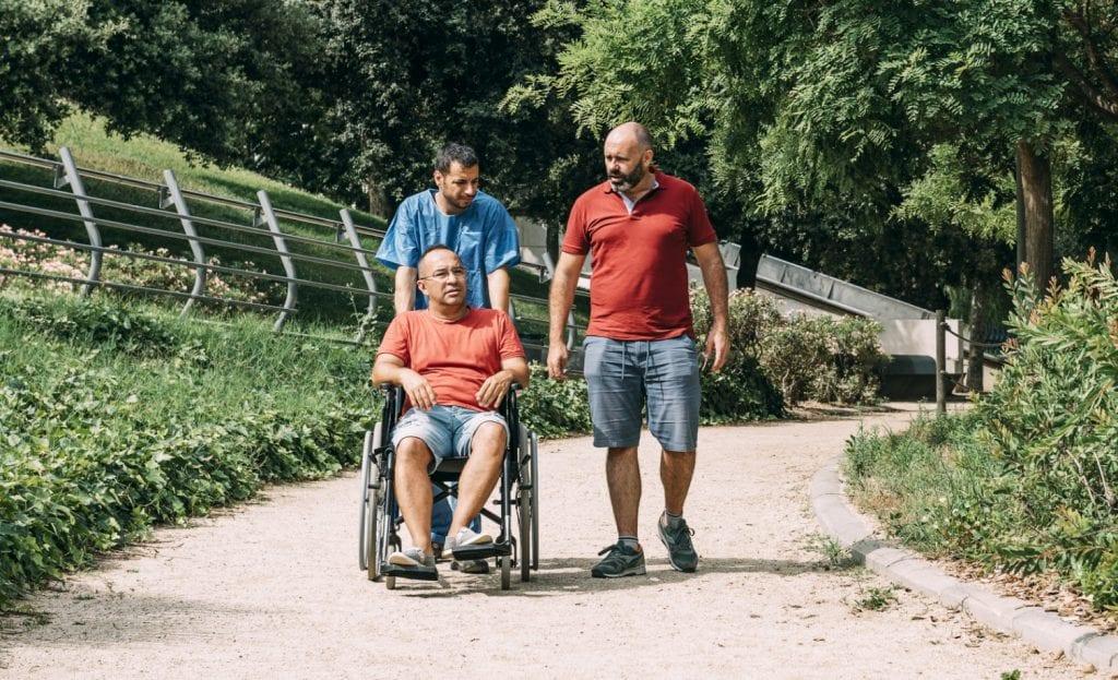 Vrienden waarvan eentje in een rolstoel zit.